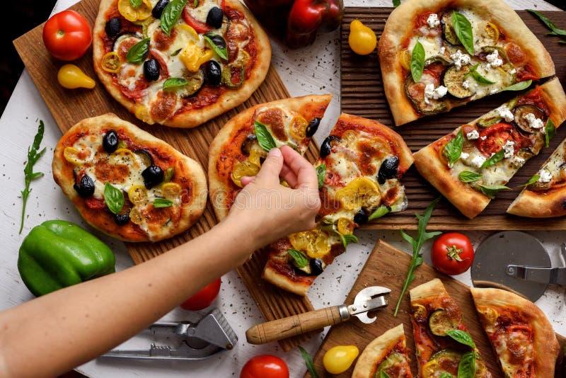 Una donna che mette le foglie di basilico sulle pizze Pizze di stile italiano fatte in casa, con olive, melanzane, peperoni, pomo immagine stock libera da diritti