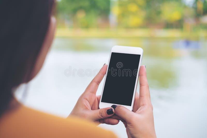 Una donna che per mezzo dello Smart Phone con lo schermo nero in bianco al fondo del lago ed all'aperto della natura immagini stock