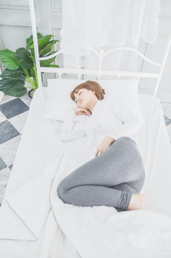 Una donna che porta un vestito bianco, sta dormendo fotografia stock libera da diritti