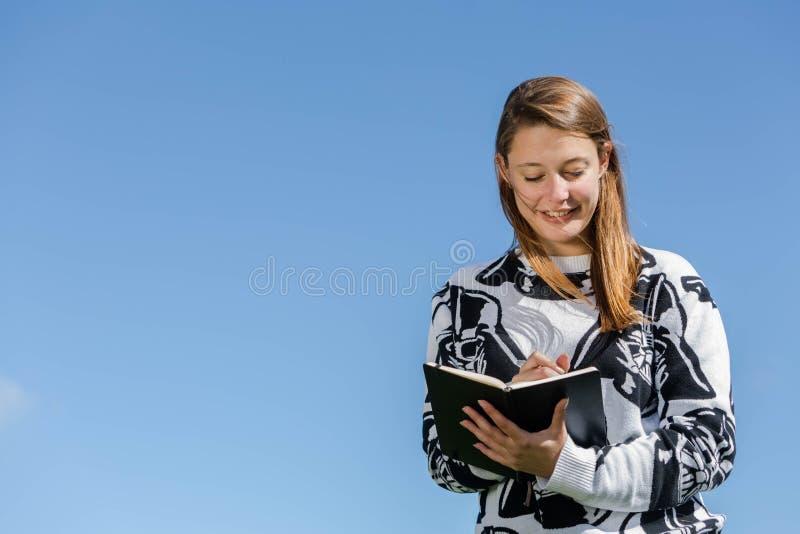 Una donna che ride e prende le note fotografia stock
