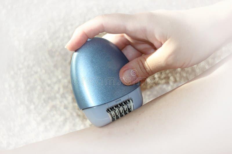 Una donna che si siede facendo uso di un depilator depilatorio Piedini regolari Epilator epilating femminile per capelli elettric fotografia stock