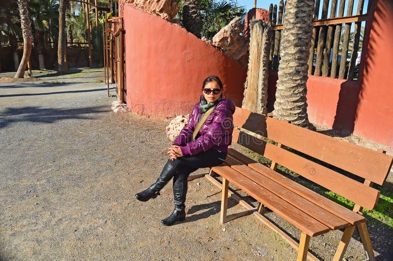 Una donna che si siede su un banco immagini stock