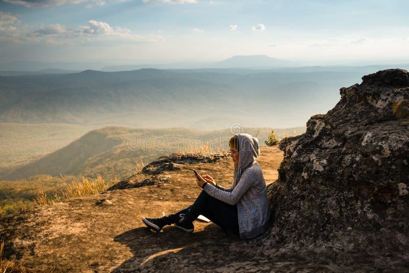 Una donna che si siede sulla montagna rocciosa facendo uso dello smartphone e che osserva fuori la bella vista naturale fotografia stock