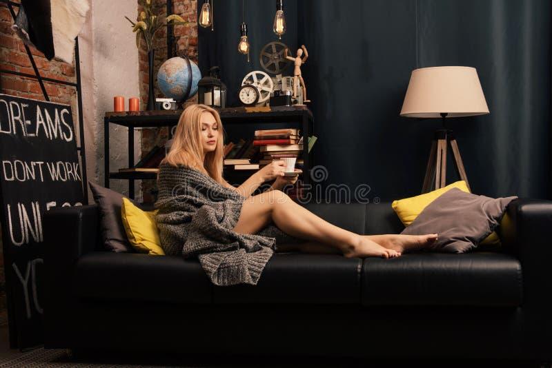 Una donna che si siede sullo strato con una tazza in sue mani e che sorride come guarda davanti lei immagini stock