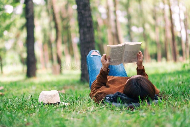 Una donna che si trova e che legge un libro nel parco fotografie stock libere da diritti