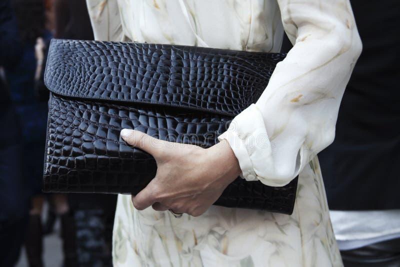 Una donna che tiene la sua borsa della frizione all'aperto fotografia stock libera da diritti