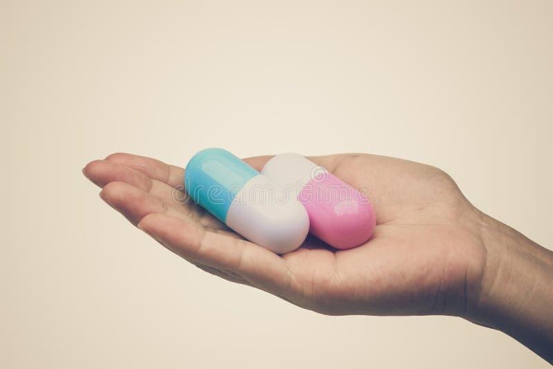 Una donna che tiene in mano due grandi farmaci per capsule immagine stock