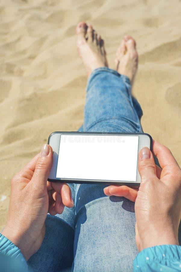 Una donna che tiene un telefono cellulare bianco con uno schermo in bianco fotografia stock libera da diritti