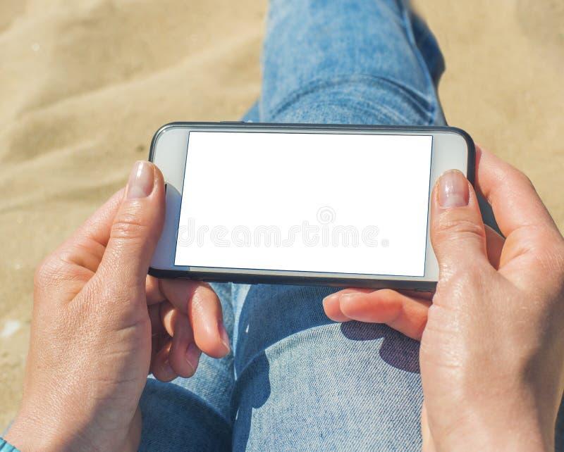 Una donna che tiene un telefono cellulare bianco con uno schermo in bianco immagine stock libera da diritti