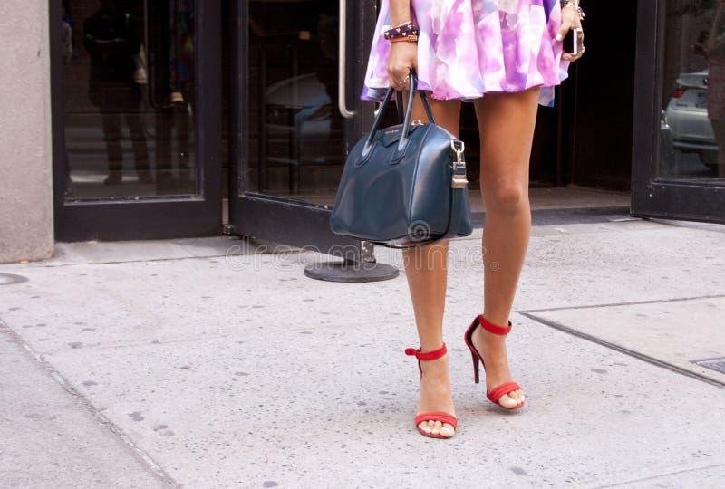 Una donna che tiene una borsa blu e che indossa le scarpe arancio fotografie stock libere da diritti