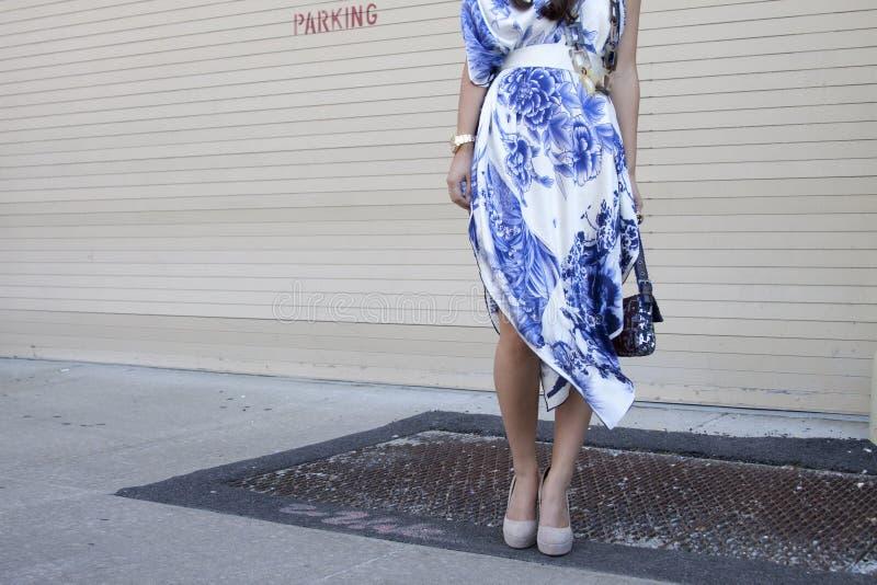 Una donna che tiene una borsa della frizione del progettista e che indossa i tacchi alti fotografia stock