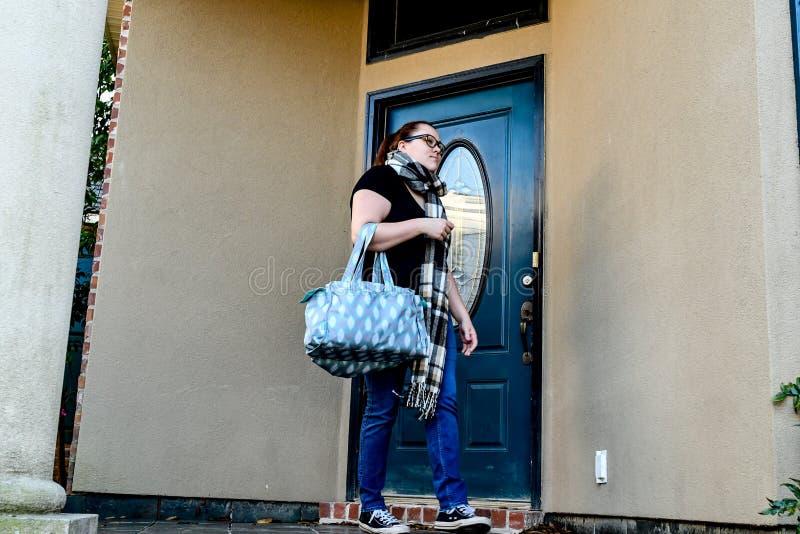 Una donna chiude la sua entrata principale a chiave mentre va via di casa con una borsa di tela oltre un braccio immagine stock libera da diritti