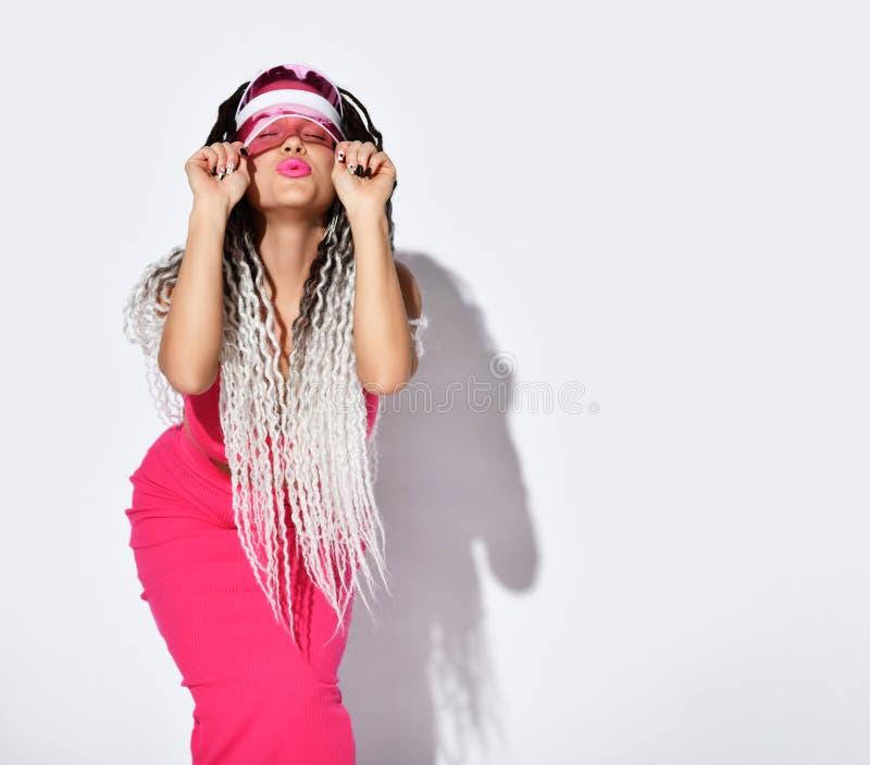 Una donna con abrasioni africane, con pigiama color rosa in alto, visore del sole, baciarti con gli occhi chiusi, posando isolati immagini stock