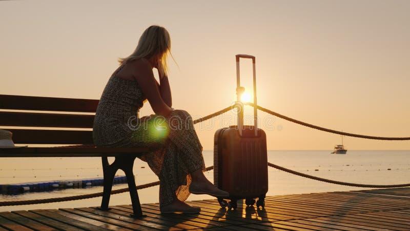 Una donna con una borsa di viaggio si siede su un pilastro di legno, guardante in avanti all'alba sopra il mare e una nave nella  fotografia stock libera da diritti