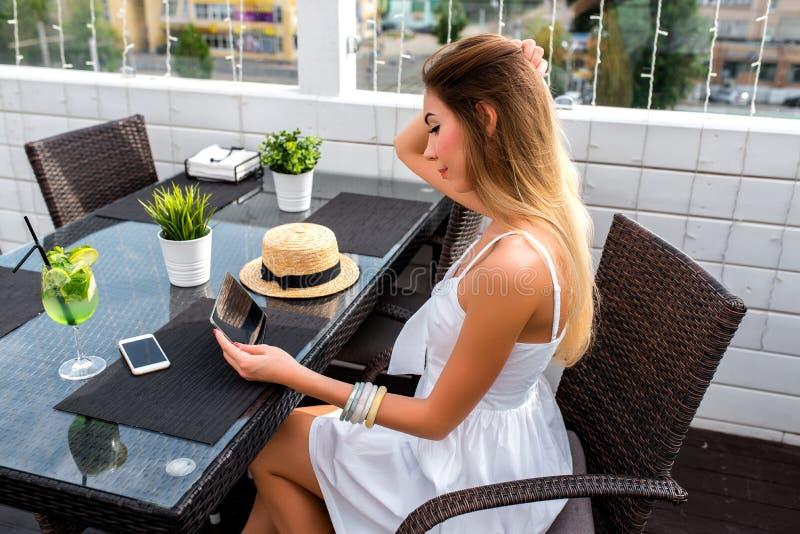 Una donna con capelli lunghi, bello caffè di estate di seduta della ragazza Compressa di sorveglianza di film Telefono della Tabe immagini stock libere da diritti