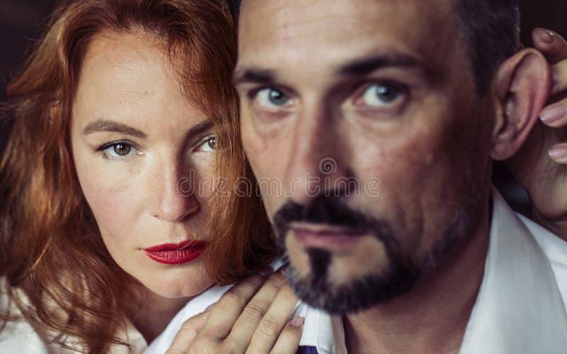 Una donna con capelli rossi e le labbra rosse che guardano direttamente nella macchina fotografica fotografie stock