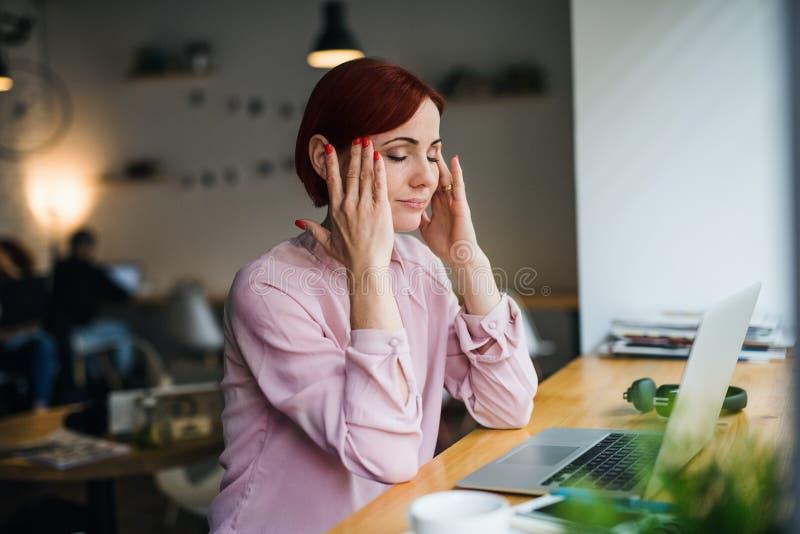 Una donna con il computer portatile che si siede alla tavola in un caffè, soffrente dall'emicrania fotografia stock libera da diritti