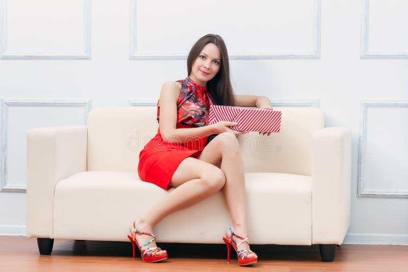 Una donna con il regalo sta sedendosi sul sofà fotografia stock