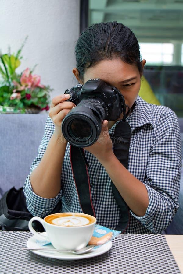 Una donna con la macchina fotografica che fotografa nel ristorante immagine stock