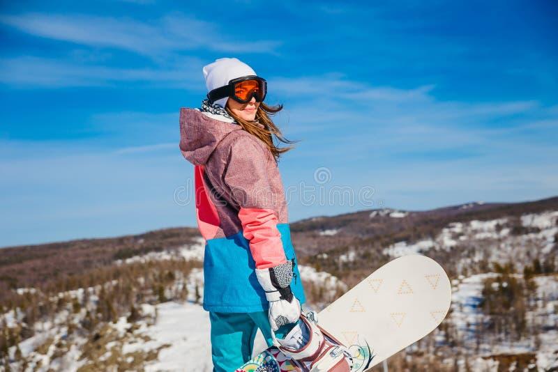 Una donna con lo snowboard sta alta nelle montagne nell'inverno immagine stock libera da diritti