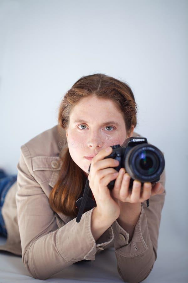 Una donna con una macchina fotografica del canone DSLR prepara prendere una foto immagine stock