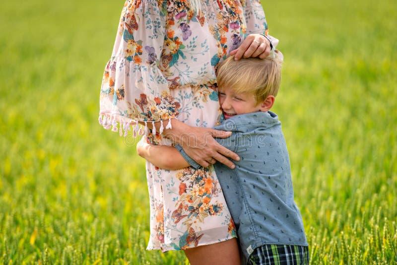 Una donna con suo figlio ha abbracciato amoroso il campo dei cereali fotografia stock