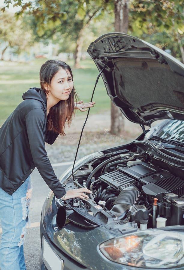Una donna con un'automobile rotta e lei aprono il cofano immagini stock libere da diritti