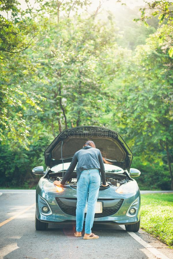 Una donna con un'automobile rotta e lei aprono il cofano fotografia stock libera da diritti