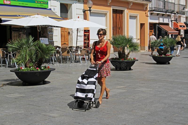 Una donna con un carrello che cammina a Calella fotografia stock