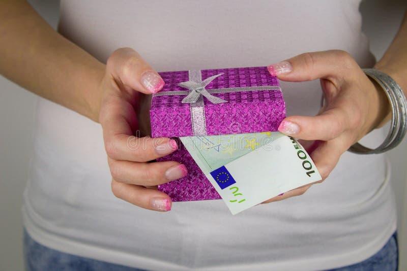 Una donna con un manicure che tiene un contenitore di regalo con cento banconote dell'euro fotografia stock libera da diritti