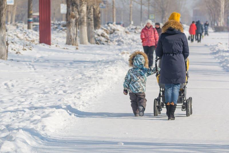 Una donna con un passeggiatore nella città nell'inverno La mamma cammina con un bambino nell'inverno fotografie stock