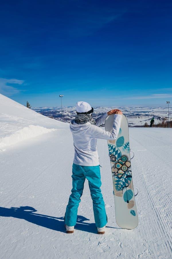 Una donna con uno snowboard è di nuovo alla macchina fotografica nell'inverno nelle montagne fotografia stock libera da diritti