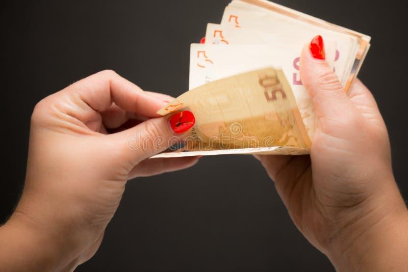 Una donna conta gli euro soldi su fondo nero immagine stock