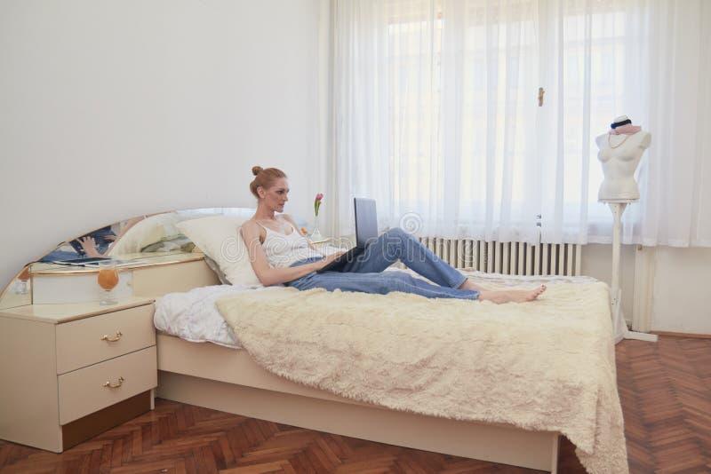 Una donna, cultura lenta, facendo uso del computer portatile, ponente a letto rilassamento grande interno ordinario della stanza  immagine stock libera da diritti