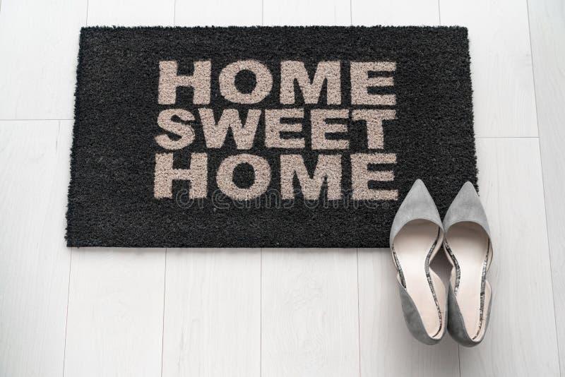Una donna d'affari di condo moderna a casa con scarpe a tallone sul formato d'ingresso che dice Home Sweet Home dare il benvenuto fotografia stock