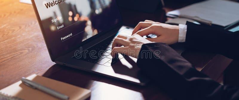 Una donna d'affari usa il computer portatile con l'iscrizione e la password per accedere al sito Web fotografia stock libera da diritti
