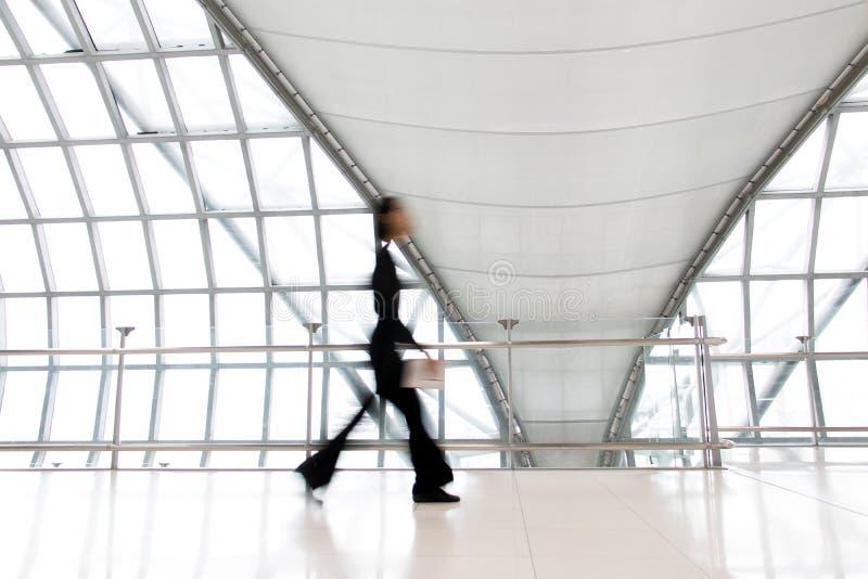 Una donna di affari che cammina nel mosso sul corridoio bianco fotografia stock libera da diritti