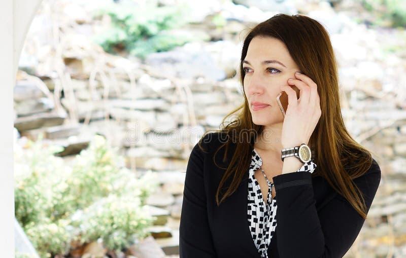 Una donna di affari seria attraente che parla su un fon mobile immagine stock