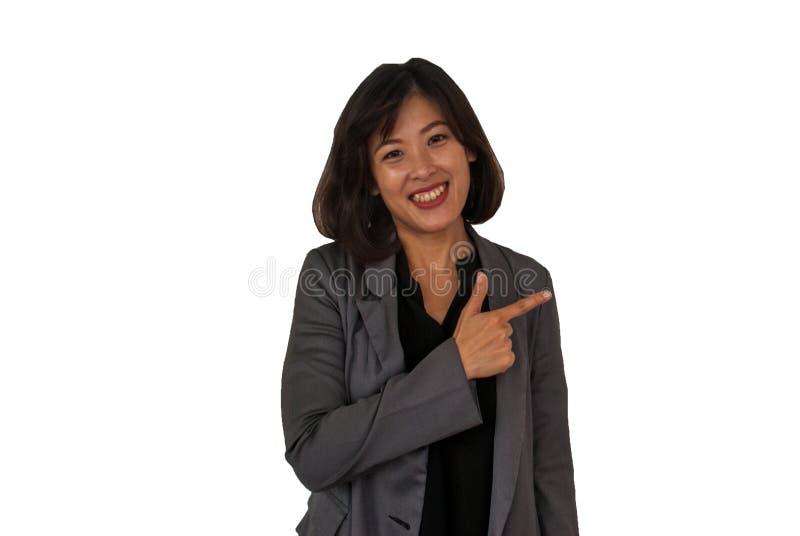 Una donna di affari sorride ed indica il suo dito l'area di copiatura su un fondo bianco fotografia stock libera da diritti