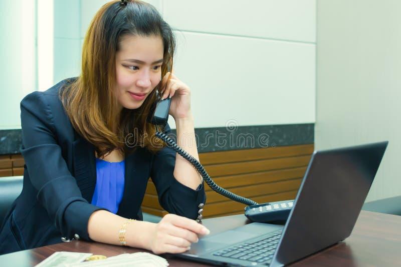 Una donna di affari sta parlando sul telefono mentre facendo uso del computer portatile fotografie stock libere da diritti