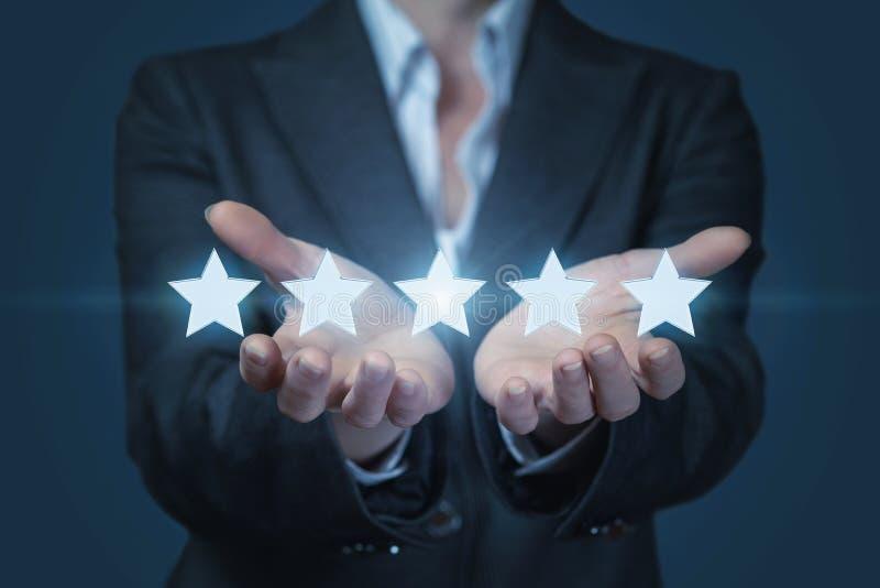 Una donna di affari sta tenendo una linea di stelle brillanti dorate ai precedenti scuri fotografie stock