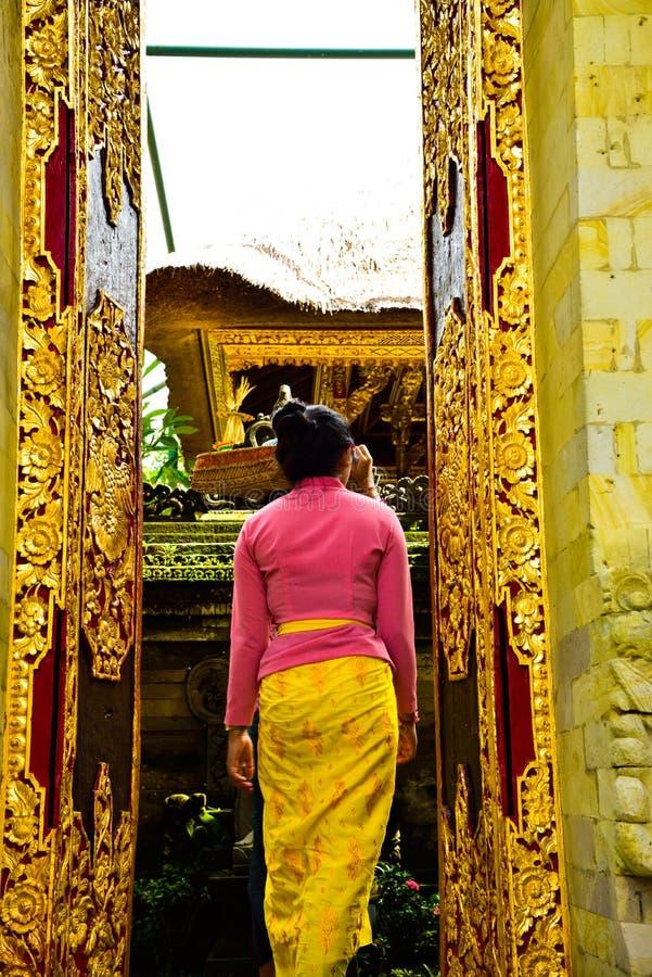 Una donna di balinese che indossa abbigliamento locale tradizionale che entra in un tempio sacro fotografia stock libera da diritti
