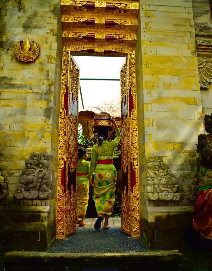 Una donna di balinese che indossa abbigliamento locale tradizionale che entra in un tempio sacro fotografie stock