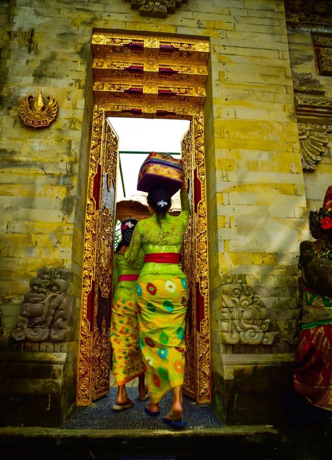 Una donna di balinese che indossa abbigliamento locale tradizionale che entra in un tempio sacro fotografie stock libere da diritti