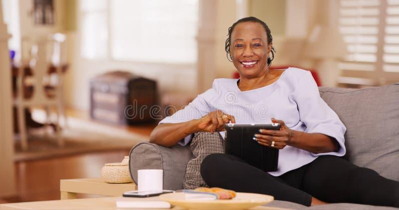 Una donna di colore anziana utilizza felicemente la sua compressa mentre esamina la macchina fotografica immagini stock