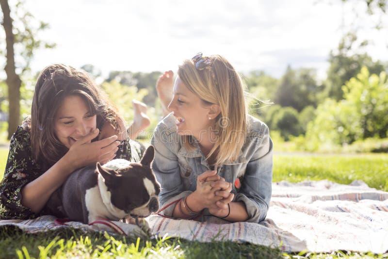 Una donna di due amici con il cane del terrier fuori al parco immagine stock libera da diritti