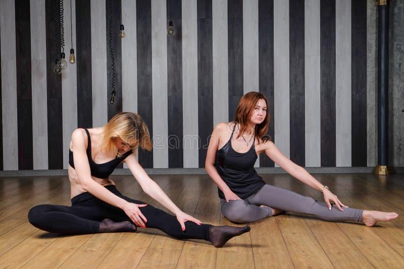 Una donna di due sport Istruttore di forma fisica Lezione con un istruttore Due donne che fanno l'allungamento di nuovo all'aiuto immagini stock libere da diritti