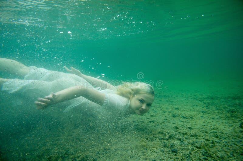 Una donna di galleggiamento Ritratto subacqueo Ragazza nel nuoto bianco del vestito nel lago Piante marine verdi, acqua immagine stock
