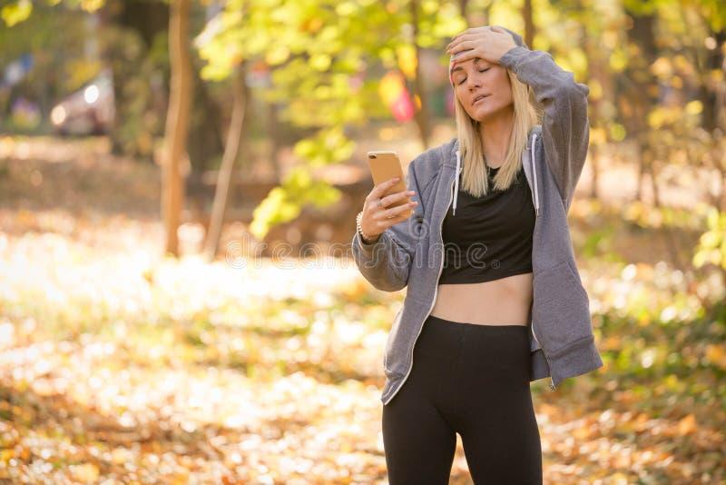 Una donna di ribaltamento tiene il suo telefono cellulare si è preoccupata per il messaggio fotografia stock
