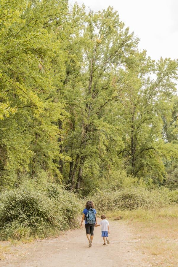 Una donna e un bambino che fanno trekking, camminando lungo una strada sterrata immagine stock libera da diritti